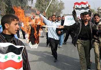 Iraqi policemen burn election posters of Interim Prime Minister Allawi